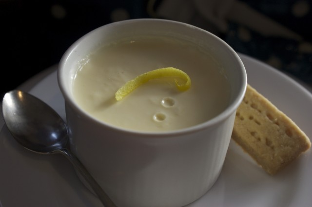 Lemon posset in ramekin with lemon zest to garnish