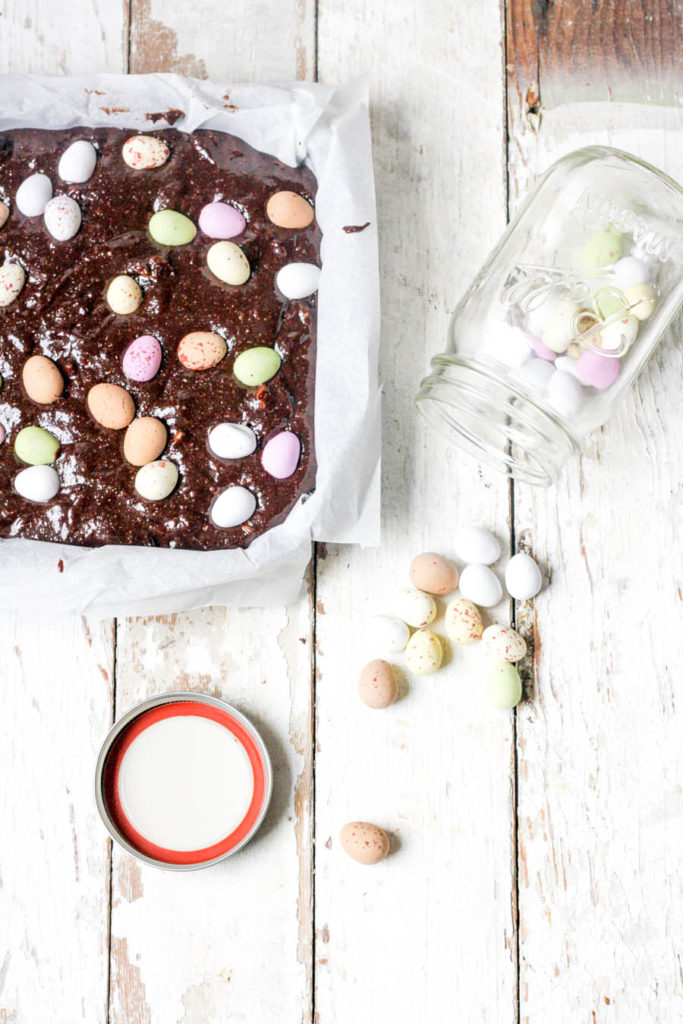 Decorating the chocolate brownies with mini eggs before they go into the oven - get the recipe on feedingboys.co.uk